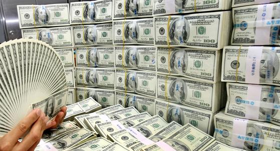 시중은행 외환창구에서 은행직원이 달러화를 살피는 모습. [중앙포토]