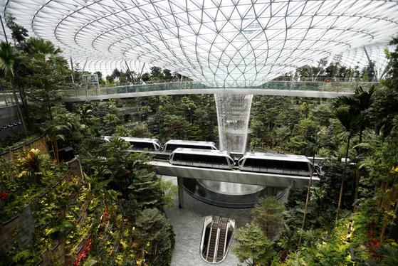넓이 4만㎡ 공간의 주얼 창이 터미널에는 실내폭포 외에도 5층 규모의 인공정원, 호텔, 식당 등 복합문화 시설이 들어서 있다. 터미널을 연결하는 열차가 실내정원을 가로지르고 있다.[로이터=연합뉴스]
