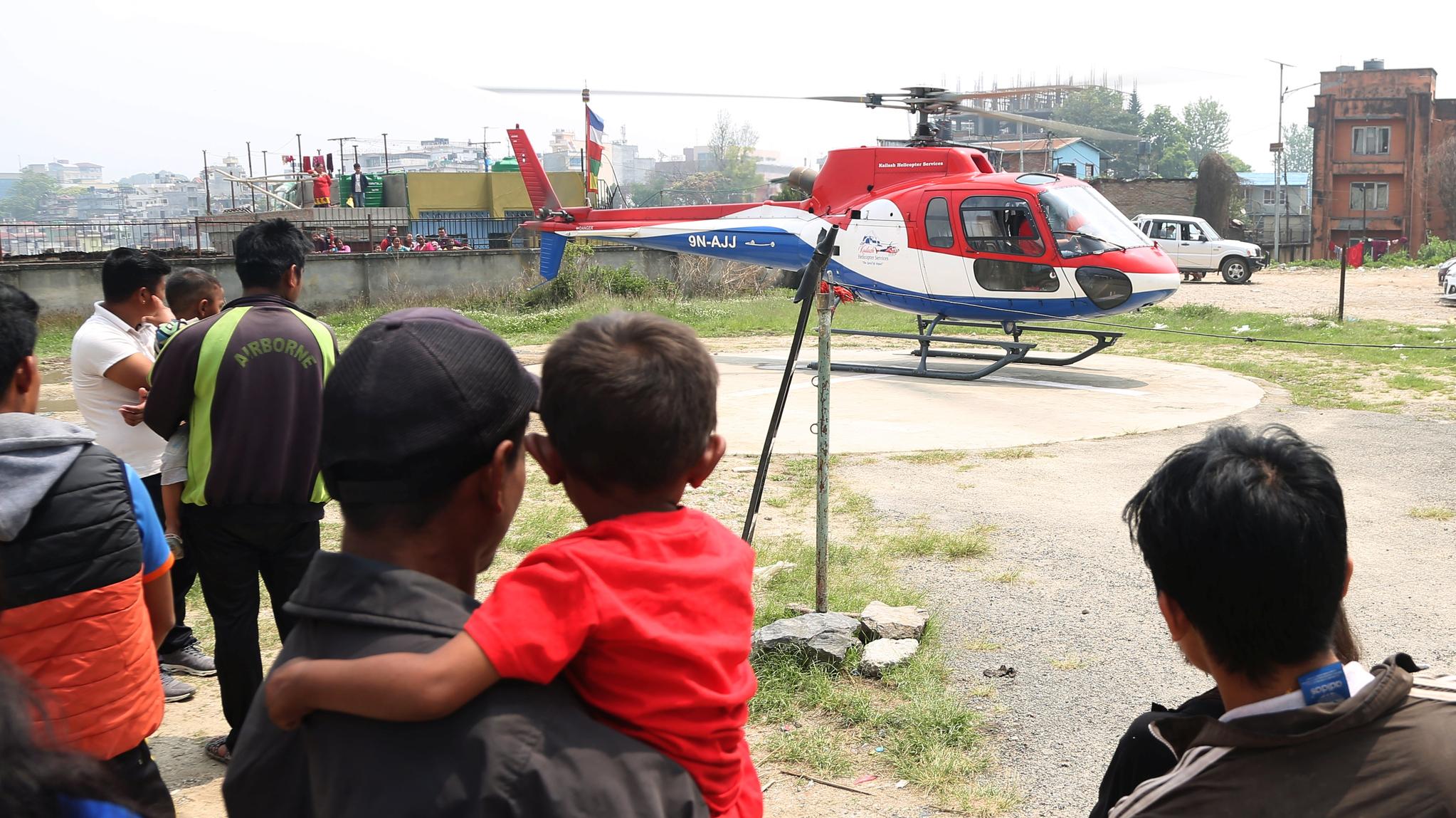 14일(현지시간) 네팔 에베레스트산 관문 루클라의 텐징-힐러리 공항에서 서미트항공 소속 소형비행기가 이륙 도중 주기된 헬리콥터와 충돌했다. 현지 주민들이 희생자를 이송하는 헬기를 바라보고 있다. [신화=연합뉴스]