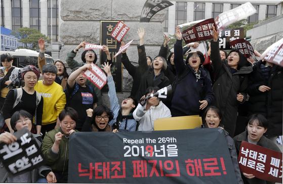 낙태죄 폐지를 주장하는 시민단체 회원들이 지난 11일 서울 종로구 헌법재판소 앞에서 기자회견을 마친 뒤 헌재의 '낙태죄 헌법불합치' 결정을 환영하며 퍼포먼스를 하고 있다. [뉴시스]