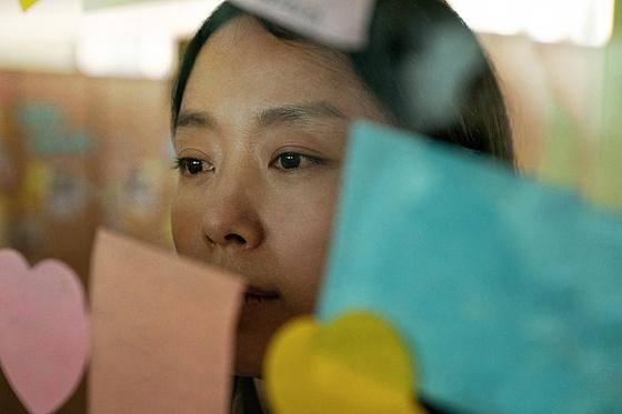 영화 '생일'에서 순남(전도연)이 세상을 떠난 아들 수호(윤찬영)가 다니던 학교를 찾은 모습. 텅 빈 교실 창문에 아이들을 기리는 쪽지가 가득하다. [사진 NEW]