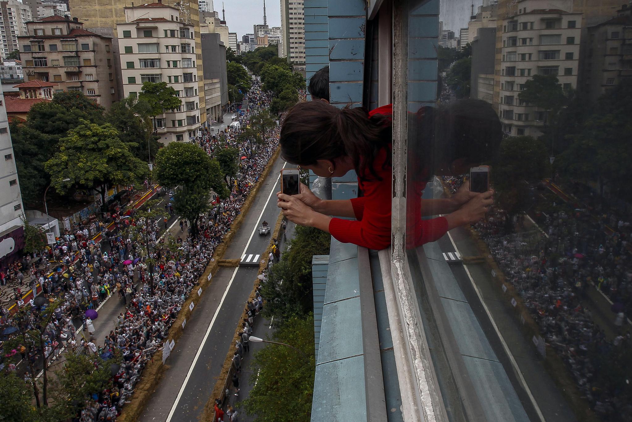 한 여성이 14일(현지시간) 브라질 상파울루에서 열린 '레드불 소프박스 레이스'를 휴대폰으로 촬영하고 있다. [AFP=연합뉴스]