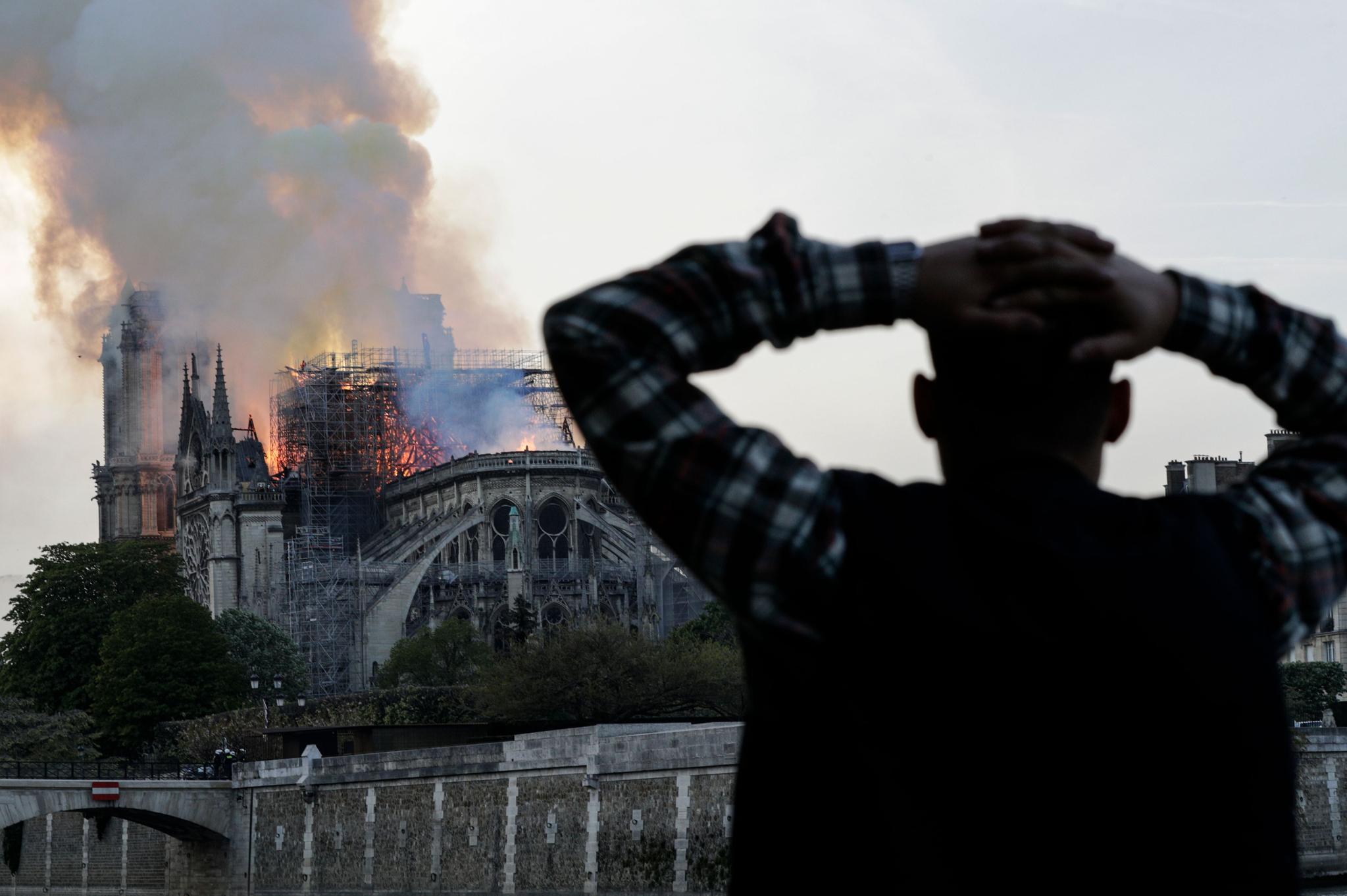 한 시민이 대성당이 불타오르는 모습을 보며 머리를 감싸고 있다. [AFP=연합뉴스]