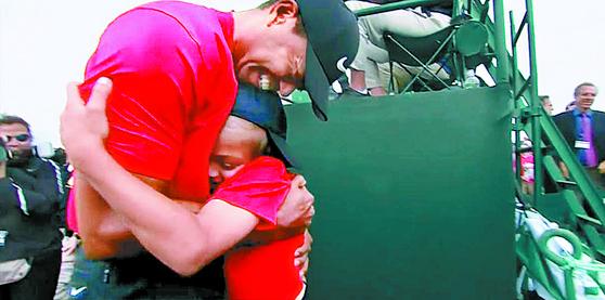 골프 황제' 타이거 우즈가 14년 만에 마스터스 정상에 오르며 화려하게 부활했다. 우즈는 불혹을 넘긴 나이에도 녹슬지 않은 기량을 과시하며 극적인 역전 우승을 일궈냈다. 우승 직후 우즈가 아들 찰리를 꼭 껴안고 기뻐하고 있다. [사진 ESPN]