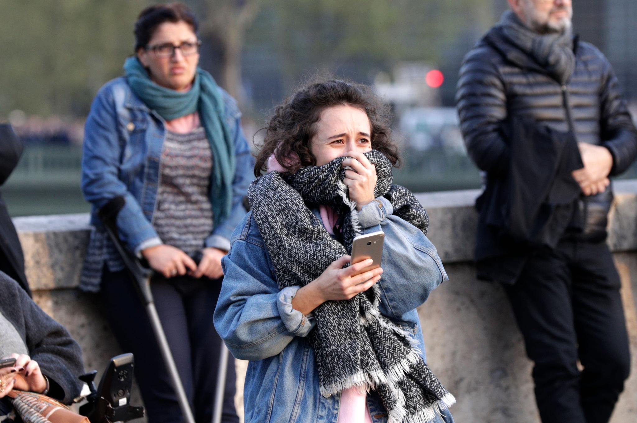 15일(현지시간) 파리 시민들이 대성당의 화재를 바라보며 안타까워 하고 있다. 이날 화재를 바라보며 눈물을 흘리는 시민들의 모습도 발견됐다. [AFP=연합뉴스]