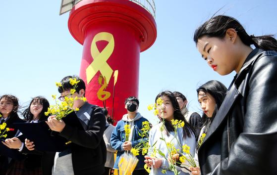 15일 전남 진도 팽목항을 찾은 영암 지역 중·고등학생과 주민들이 제주에서 가져온 유채꽃을 들고 세월호 희생자를 추모하고 있다. [프리랜서 장정필]