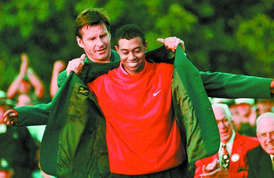 닉 팔도가 1997년 마스터스에서 메이저 첫 우승을 차지한 우즈(오른쪽)에게 그린 재킷을 입혀주고 있다. [AP=연합뉴스]