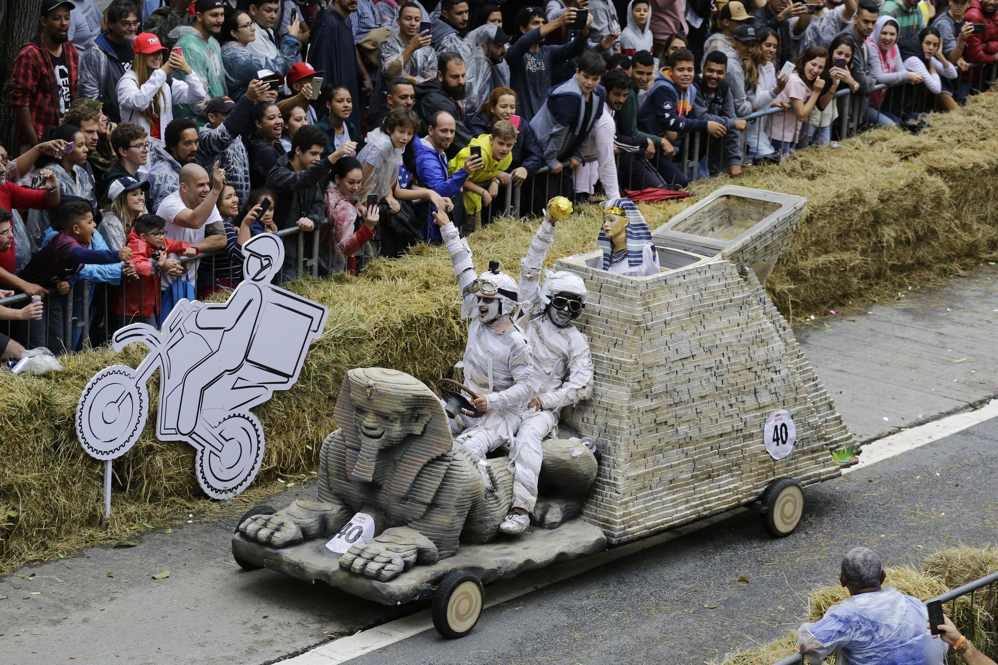 스핑크스 모양의 차를 탄 참가자들이 14일(현지시간) 브라질 상파울루에서 열린 '레드불 소프박스 레이스'에서 장애물을 통과한 뒤 기뻐하고 있다. [AP=연합뉴스]