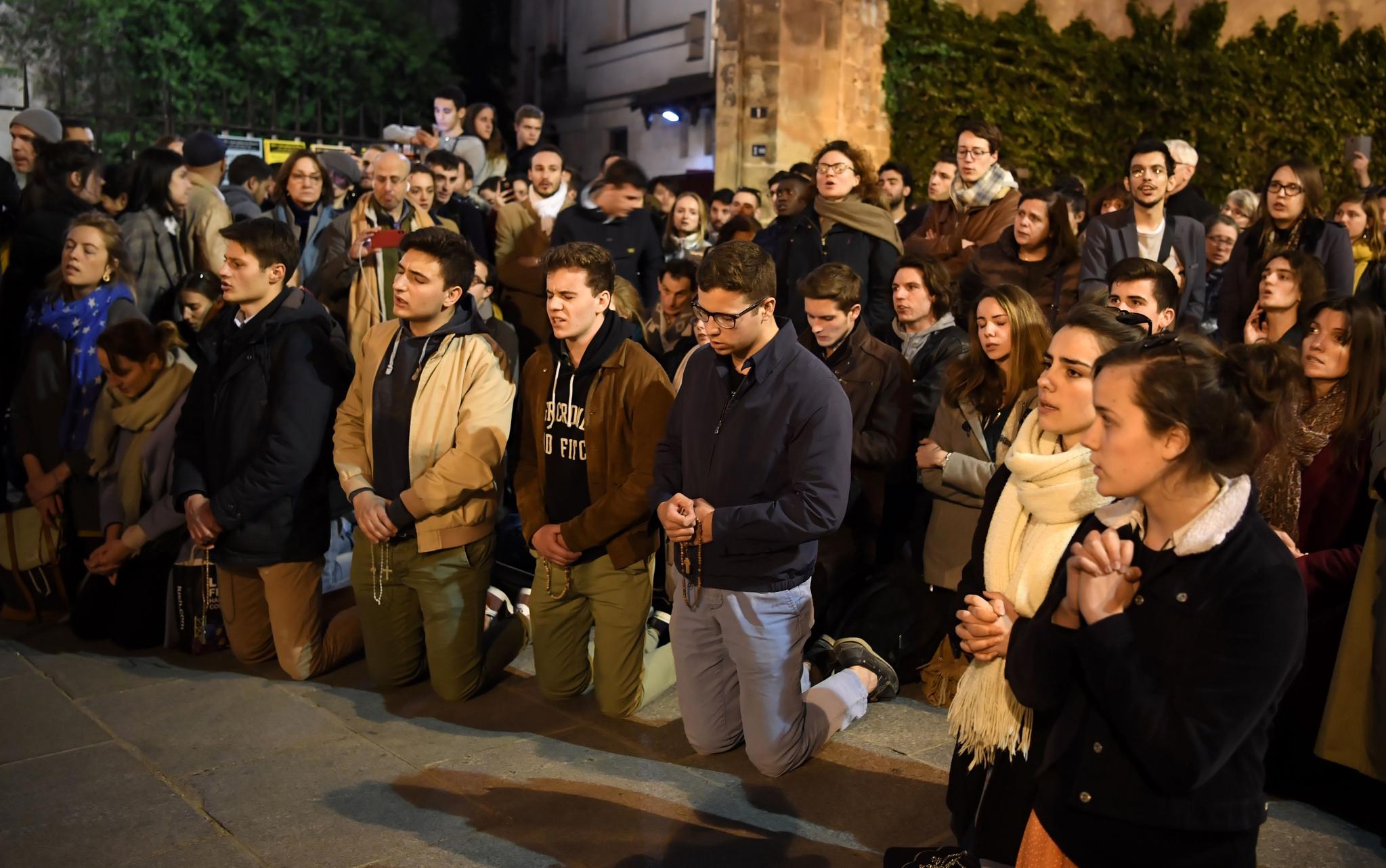 파리 시민들이 무너져 내리는 파리 노르트담 대성당을 바라보며 무릎을 꿇고 기도를 하고 있다. [AFP=연합뉴스]