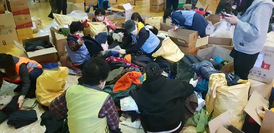 강원 산불 자원봉사들이 기부품으로 온 헌 옷을 정리하고 있다. [사진 권미영 한국중앙자원봉사센터장]