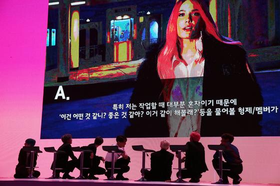할시의 영상 인터뷰를 지켜보는 방탄소년단. 자막을 가리지 않기 위해 바닥에 앉은 모습. [연합뉴스]