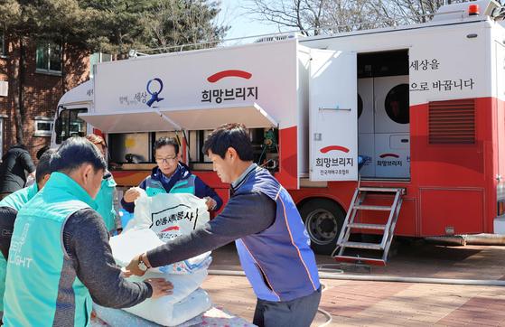 현대ㆍ기아차 임직원들이 강원도 산불 피해 지역에 투입된 현대차그룹의 '도시형 세탁구호차량'과 함께 세탁 봉사를 하고 있다. [사진 현대차그룹]
