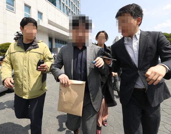 지난 9일 울산지방경찰청에서 지능범죄수사대 사무실을 압수수색한 검찰 관계자가 서류 봉투를 들고 건물을 나서고 있다. [연합뉴스]