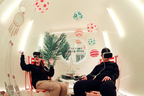 LG유플러스는 서울 강남역 인근에 5G가 가져온 변화를 체감할 수 있는 팝업스토어 '일상로5G길'을 오픈했다. 방문객들이 가상현실(VR) 체험 존에서 VR기기를 착용한 채 실감형 콘텐트를 즐기고 있다. [사진 LG유플러스]