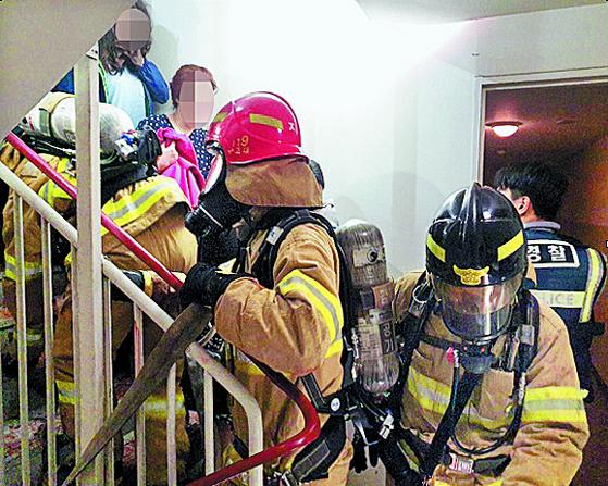 이날 오전 사건이 발생한 아파트 계단에서 대피하는 주민들과 출동한 경찰·소방대원들이 뒤섞여 있다. [뉴시스]