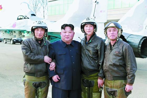 김정은 위원장이 16일 공군기지를 방문해 조종사들과 촬영한 사진을 조선중앙통신이 공개했다. [연합뉴스]