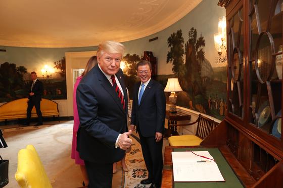 한미 정상회담을 위해 워싱턴을 방문한 문재인 대통령이 지난 11일(현지시간) 백악관에 도착해 방명록을 작성하고 있다. 도널드 트럼프 미 대통령이 방명록 내용을 보고 엄지 손가락을 들어보이고 있다. [청와대사진기자단]