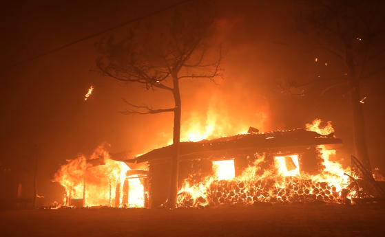 지난 4일 오후 7시17분쯤 강원 고성군 토성면 원암리 한 주유소 맞은편 도로변 전신주에서 시작된 것으로 추정되는 불이 나 한 식당이 불타고 있다. [연합뉴스]