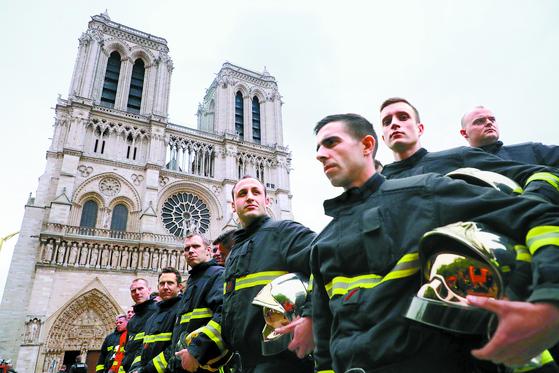 16일 프랑스 파리의 노트르담 대성당 앞에서 소방대원들이 화재 진압을 마친 뒤 크리스토프 카스타네르 내무장관과 로랑 뉘네 차관의 방문을 기다리고 있다. [EPA=연합뉴스]