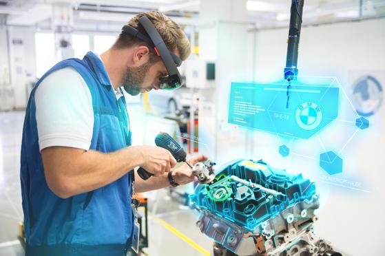 VR기술을 적용한 엔진조립 과정을 시각화한 모습. BMW 엔진조립 아카데미 참가자들이 VR고글을 쓰고 엔진조립 과정 교육을 받고 있다. [사진 BMW]