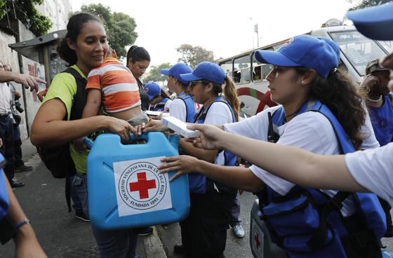 인도주의적 위기를 겪고 있는 베네수엘라에 대한 국제 인도주의 기관의 구호가 처음 시작된 16일 수도 카라카스에서 아이를 안은 한 여성이 베네수엘라 적십자사 마크가 그려진 물통과 식수정화용 소독약품을 받고 있다. [AP=연합뉴스]