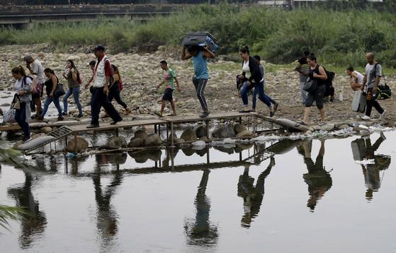 지난 14일 베네수엘라 주민들이 국경을 불법으로 넘어 이웃 나라인 콜롬비아로 들어서고 있다. 베네수엘라에선 경제 위기가 본격화한 지난 2015년 이후 인구의 10%인 300만 명이 콜롬비아 등 이웃국가로 이주했다. [AP=연합뉴스]