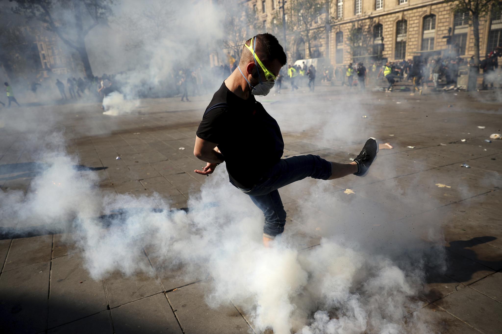 한 남성이 20일(현지시간) '노란 조끼' 시위에서 경찰이 쏜 최루탄을 발로 차고 있다. [AP=연합뉴스]