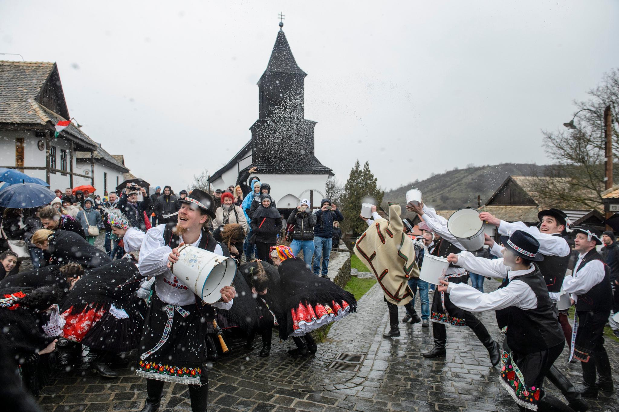 지난해 헝가리 호로쾨에서 전통의상을 입은 남자들이 양동이로 여자들에게 물을 뿌리고 있다. 홀로쾨는 유네스코 세계문화유산으로 지정된 마을이다. [AP=연합뉴스]