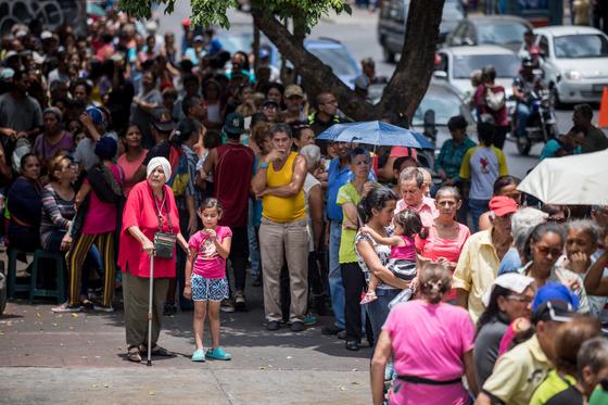 지난 18일 베네수엘라 수도 카라카스의 한 병원 앞에서 주민들이 물통과 정화용 소독약품으로 이뤄진 식수 키트를 받기 위해 줄지어 서있다. [EPA=연합뉴스]