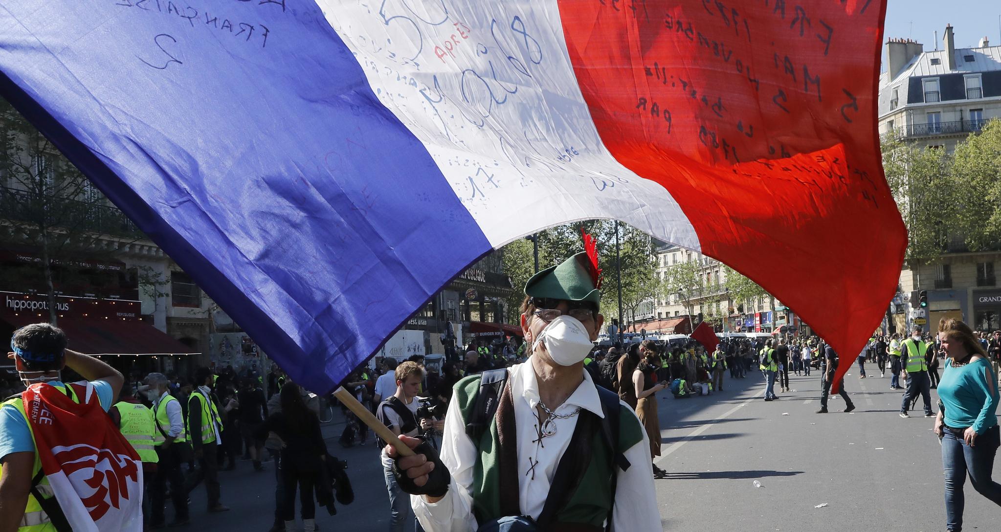 지난 20일(현지시간) 프랑스 파리에서 발생한 '노란 조끼' 시위에서 한 남성이 국기를 흔들고 있다.[AP=연합뉴스]