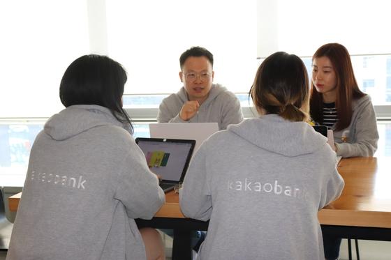 카카오뱅크 직원들이 그레이 컬러 회사 후드를 입고 회의 중이다. [사진 카카오뱅크]