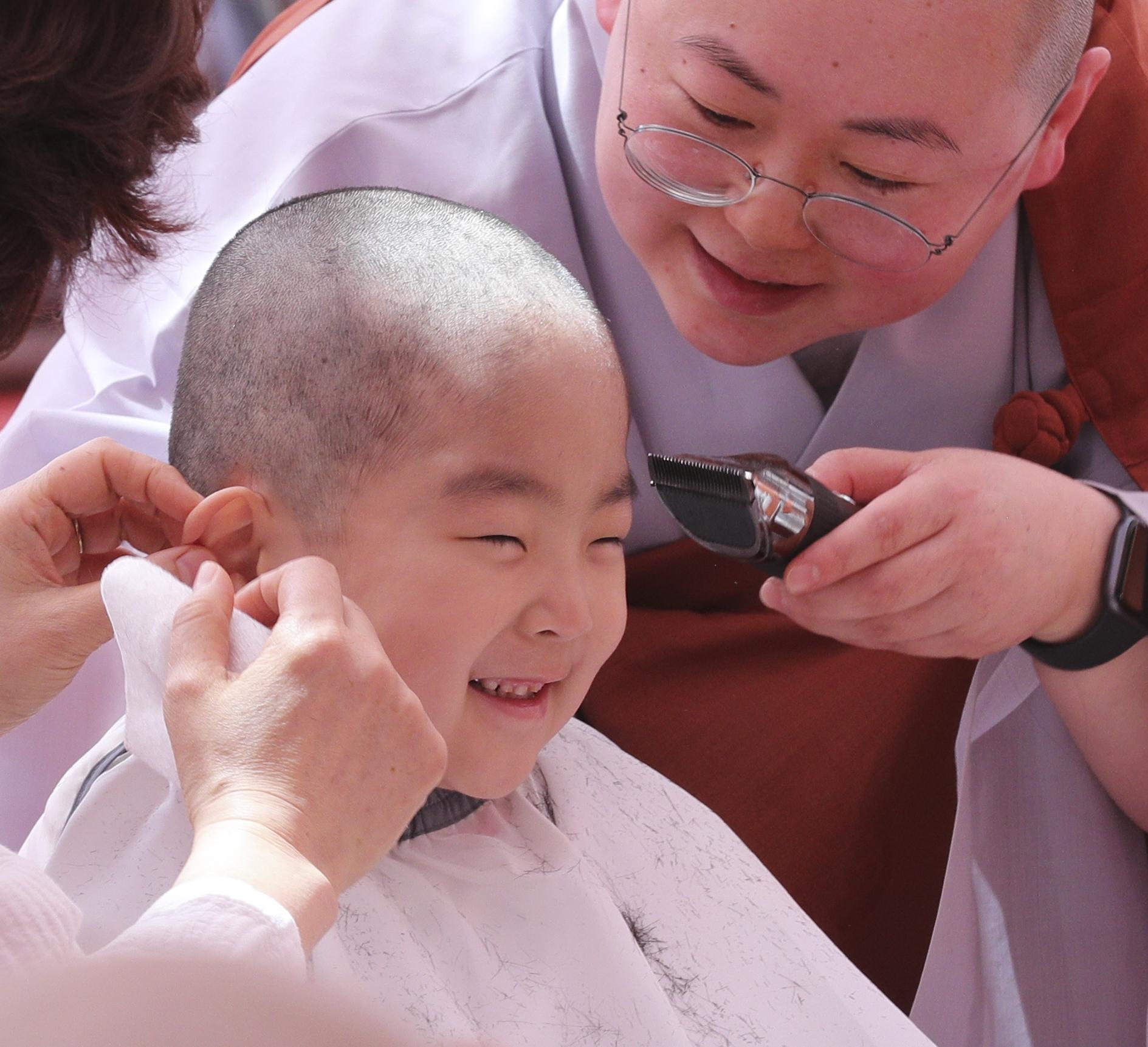 한 동자승이 단기출가 삭발 수계식이 열린 22일 서울 종로구 조계사에서 스님이 머리를 깎자 밝게 미소 짓고 있다.     임현동 기자
