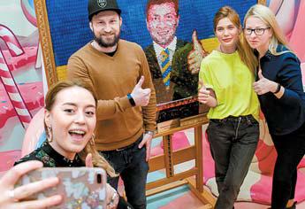 지난 18일 러시아 상트페테르부르크에서 한 뮤지엄 단원들이 사탕으로 만든 젤렌스키의 초상화 옆에서 셀카를 촬영하고 있다. [로이터=연합뉴스]