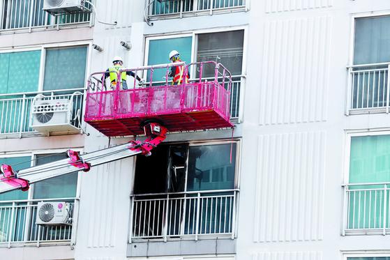 진주시 방화·살인 참사가 난 아파트 외벽을 새로 칠하고 있다. 주민들은 검게 탄 외벽을 볼 때마다 참사가 떠오른다며 개선을 요구했다. [연합뉴스]