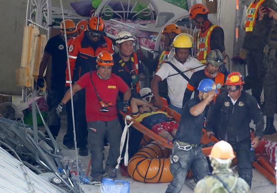 23일(현지시간) 필리핀 팜팡가주(州) 포락 마을에서 구조대원들이 지진으로 무너진 한 상가 건물 잔해에서 생존자를 구출해 옮기고 있다. [AP=연합뉴스]