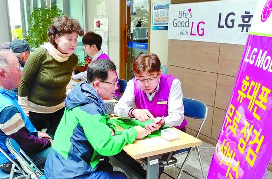 LG전자 직원들이 지난 11일 경남 창원 마산 노인종합복지관을 찾아 고객들에게 휴대폰 서비스를 제공하고 있다. [뉴스1]