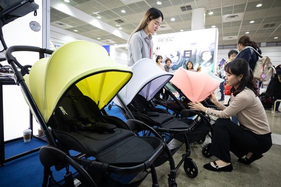 18일 서울 강남구 코엑스에서 열린 '코베 베이비페어'를 찾은 관람객들이 다양한 임신, 출산, 육아 용품을 둘러보고 있다. [뉴스1]