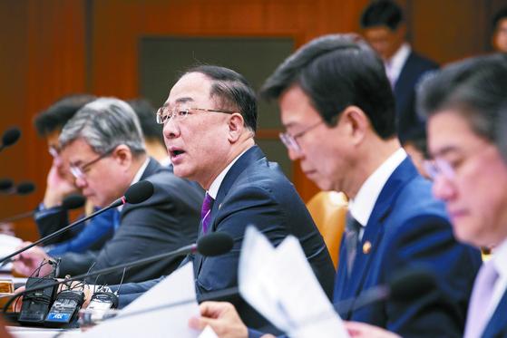 """홍남기 부총리(가운데)는 23일 산업경쟁력 강화 관계 장관회의에서 '채권단은 아시아나항공에 1조6000억원을 투입해 자본을 확충하고 유동성 문제를 해소할 계획""""이라고 말했다. [뉴스1]"""