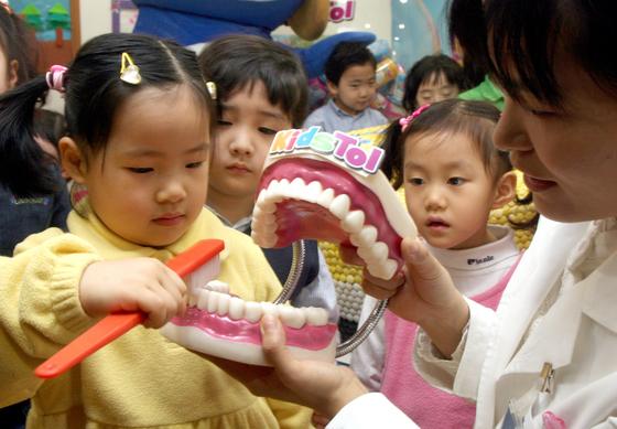 치과의사의 지도에 따라 칫솔질 요령을 배우는 어린이집 원생의 모습. 어린이는 어른과 다른 존재다. 이들의 성장, 체형, 심리를 고려해 어른과 다른 의료 서비스가 제공되어야 한다. [중앙포토]