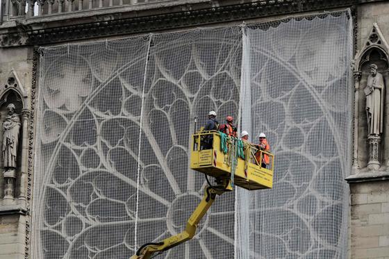 전문가들이 23일(현지시간)프랑스 파리 노트르담 성당에서 방수포 설치 작업을 하고 있다. [AFP=연합뉴스]