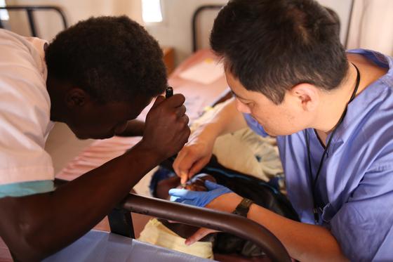 감비아인 자원봉사자 부바와 마취과 전문의 이숭규씨가 환자 눈을 마취하고 있는 모습. 마취과 전문의가 캠프에 동행하면 같은 기간에 더 많은 환자들을 수술할 수 있다. [사진 비전케어]