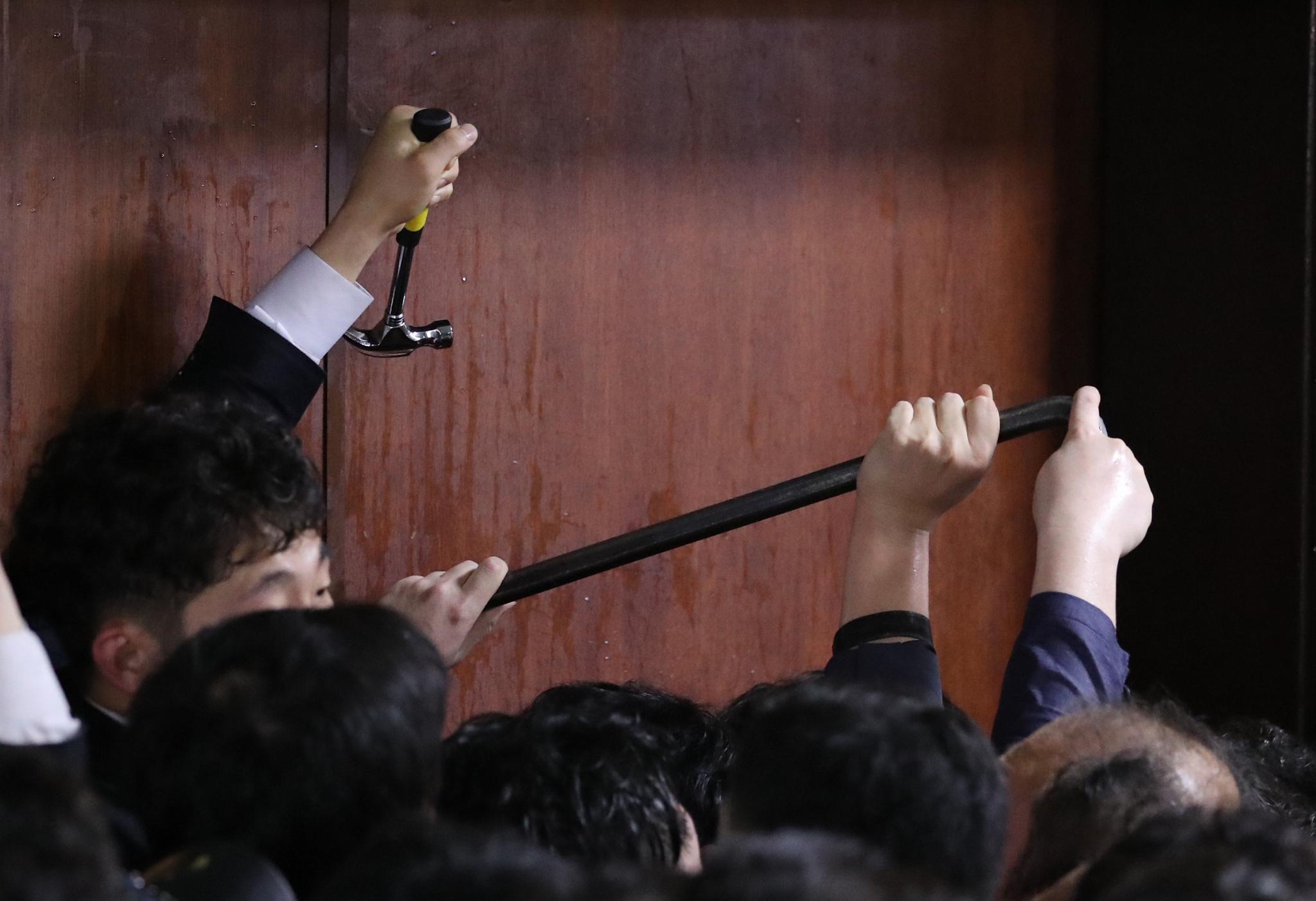 더불어민주당 의원과 보좌관들이 26일 새벽 여야4당의 수사권조정법안을 제출하기 위해 자유한국당 당직자들이 점거하는 국회 의안과에 '도구'를 사용해 진입 시도하고 있다. [연합뉴스]