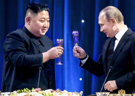 김정은 북한 국무위원장과 블라디미르 푸틴 러시아 대통령이 25일 정상회담 후 만찬에서 건배하고 있다. [연합=타스통신]
