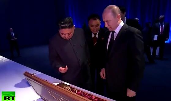 김정은 위원장이 25일 푸틴 대통령과의 만찬에서 건네받은 동전을 떨어뜨린 뒤 아래를 쳐다보는 장면. [러시아 RT방송 유튜브 캡처]