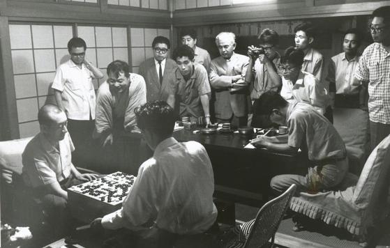 바둑의 전설 기성 우칭위안은 사소취대를 취할 줄 아는 사람이었다. 1962년 제1기 명인전 리그 최종국에서 우칭위안(왼쪽)과 사카다(오른쪽)가 종국(終局) 직후 기원 관계자들에게 둘러싸인 모습.[사진제공=일본기원]