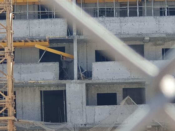 블라디보스토크 한 건설 현장에서 28일(현지시간) 북한 노동자가 합판을 옮기는 작업 중이다. 안전모 1개가 유일한 안전 장치였다. 이 노동자가 서있는 곳은 건물 11층 높이다. 블라디보스토크=전수진 기자