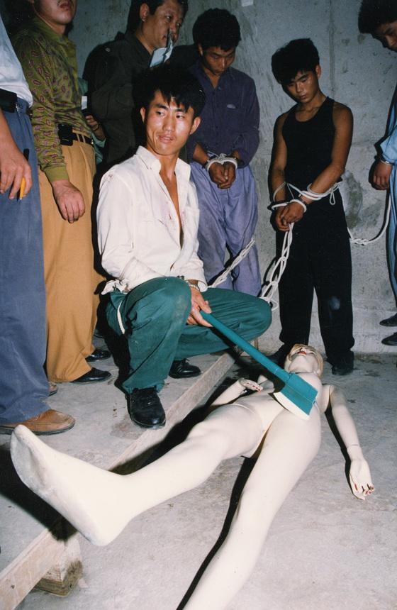 김현양이 아지트에서 피해자 대역인 마네킹을 도끼로 내리치는 장면을 재연하고 있다. [한국 사진기자회 10대 뉴스 제공]