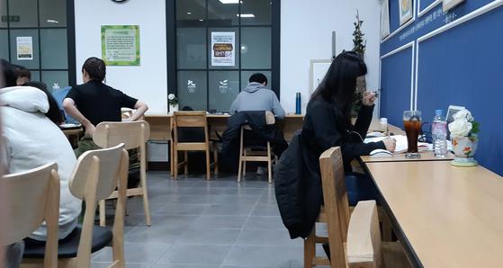 내가 자주 찾는 도서관 북카페에는 편한 마음으로 공부하는 사람이 많다. 안내문에는 집중을 원하는 사람은 열람실로 올라가도록 정중히 권유하여 카공족과 커피 손님들 사이의 공존을 도모하고 있다. [사진 박헌정]