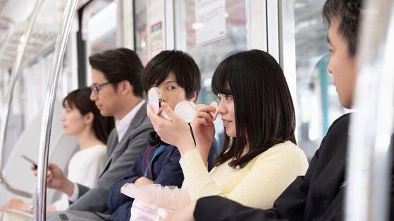 전철 내 화장하는 여인을 바라보는 장면을 광고에 실은 일본 기업. [사진 도큐철도]