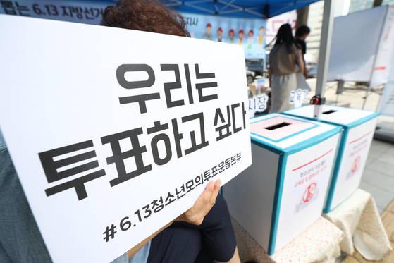 전국동시지방선거일인 지난해 6월 13일 오후 서울 종로구 광화문에서 촛불청소년인권범제정연대 회원들이 선거연령 하향과 청소년 참정권 보장을 촉구하는 집회를 열고, 모의투표 부스를 운영하고 있다. [연합뉴스]